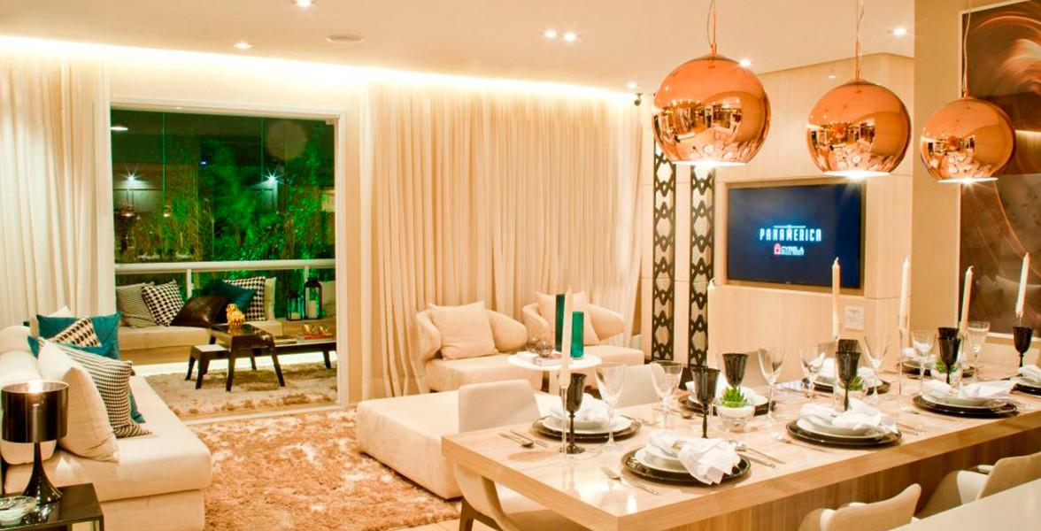 LIVING AMPLIADO do apto de 92 m², conforme modelo decorado, com vista para o terraço com guarda-corpo de vidro.