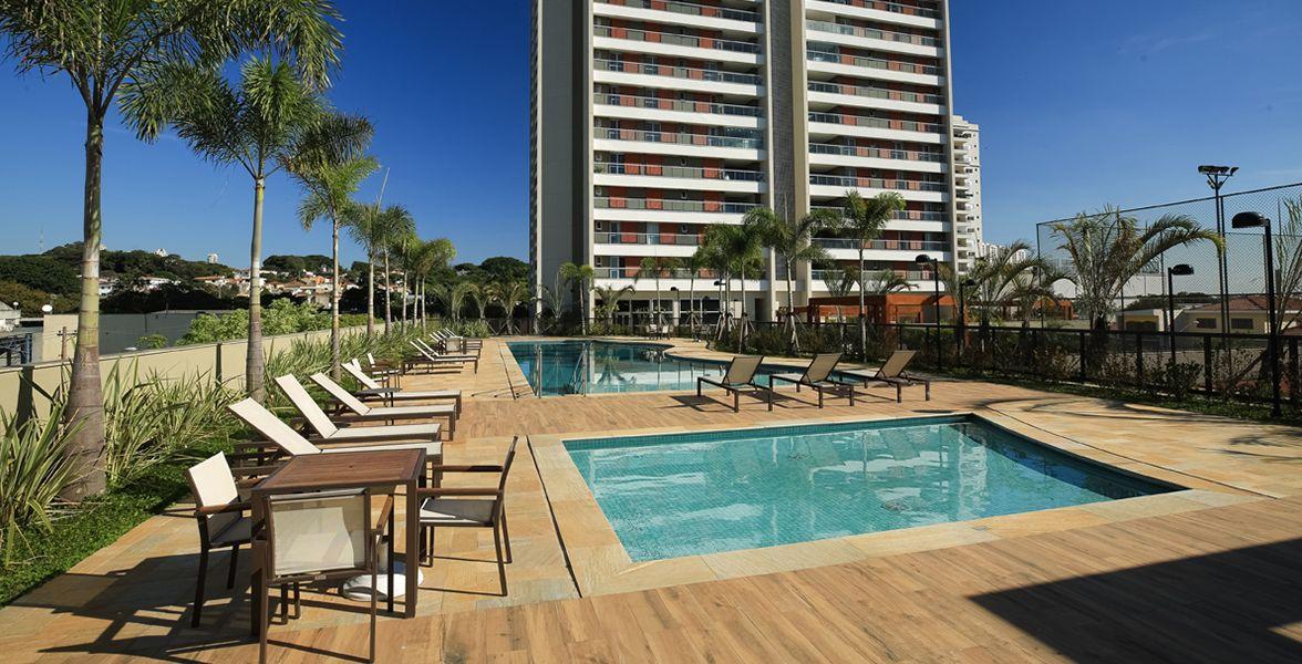 PISCINA adulto com deck molhado e ao fundo, a piscina infantil e um solarium com ilha e reflexologia.
