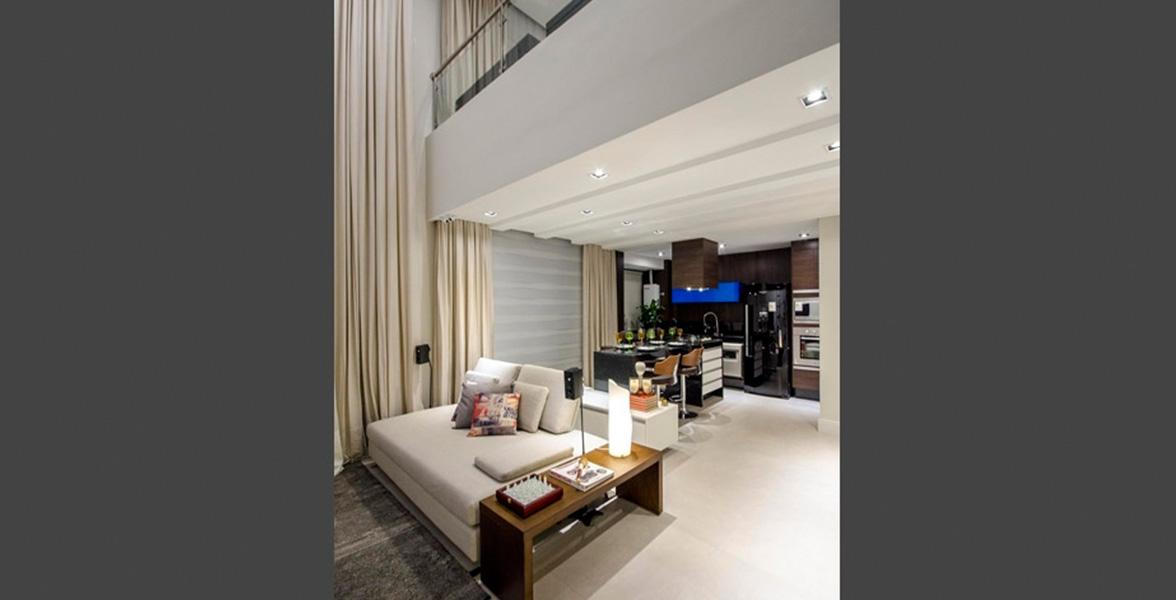 LIVING do apto de 76 m² integrado à cozinha e pé-direito duplo.