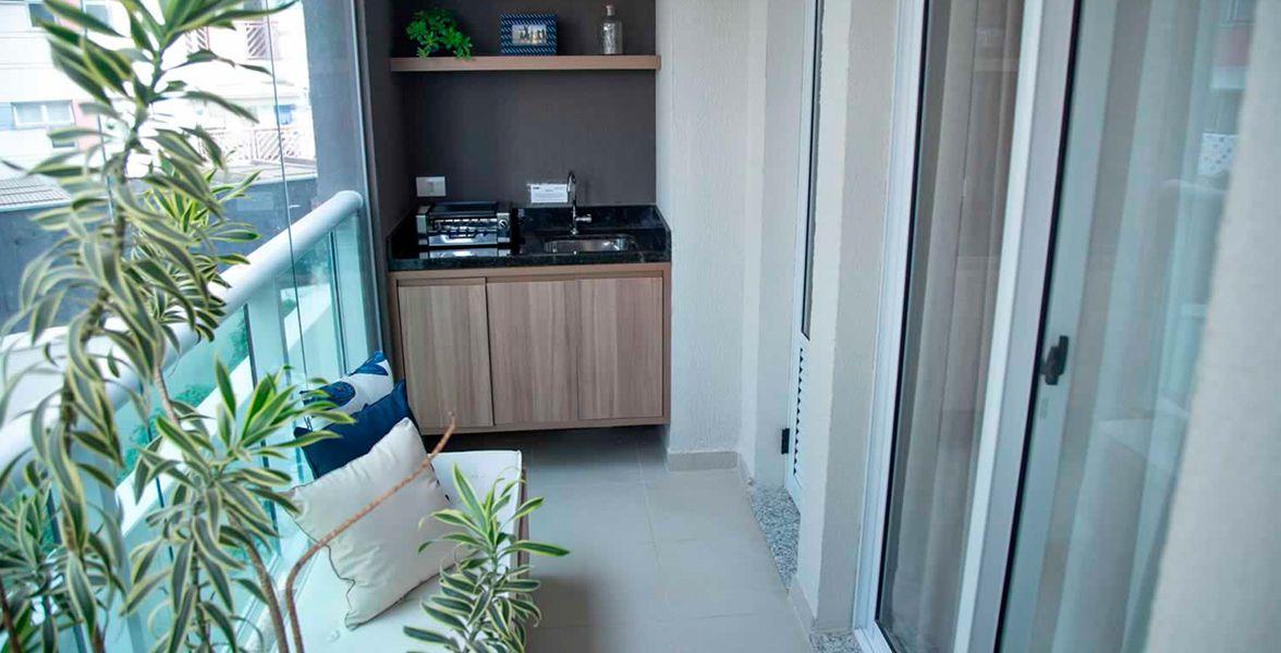 TERRAÇO GRILL do apto de 61 m² com guarda-corpo de vidro.