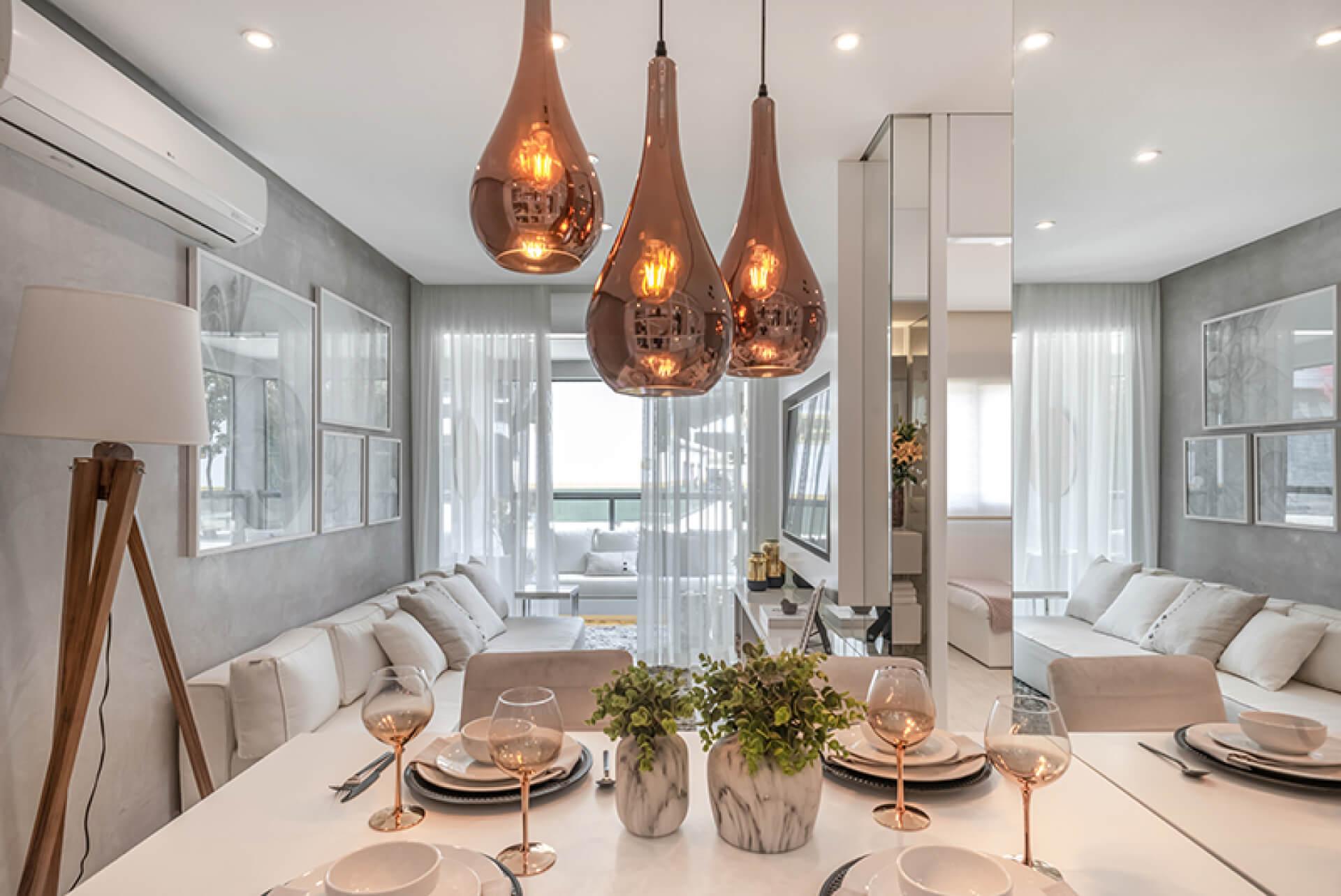 LIVING do apto de 59 m² que integra as salas de jantar e estar, favorecendo o convívio entre os ambientes. A varanda é uma extensão da área social que possui guarda-corpo em vidro, proporcionando vista da região e maior entrada de iluminação natural.