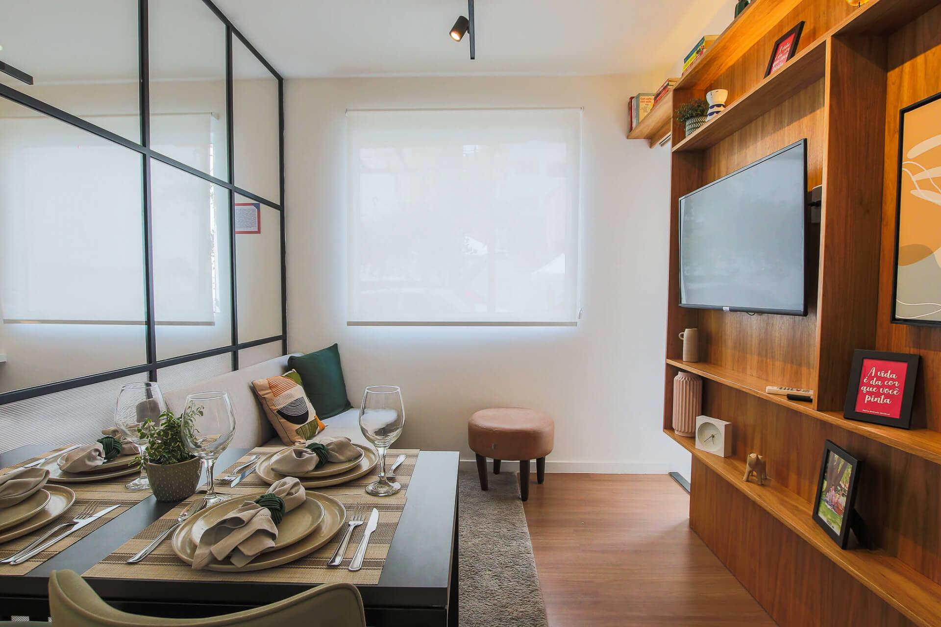 SALA do apto de 25 m² vista da entrada do apartamento. A área social e o dormitório são iluminados naturalmente por aberturas, que proporcionam um ambiente arejado e uma residência salubre.